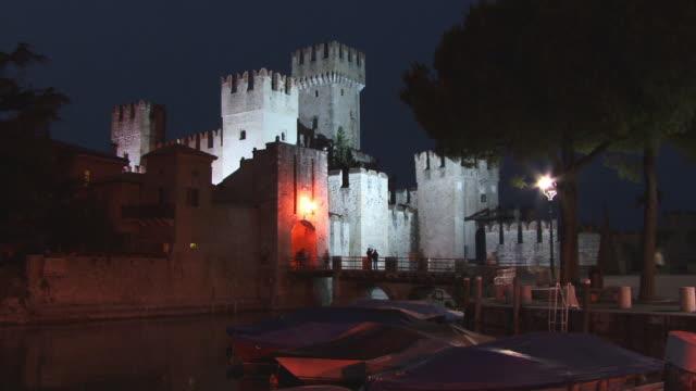 vídeos de stock e filmes b-roll de fast motion, ws, scaliger castle illuminated at night, sirmione, lombardy, italy - circa 13th century