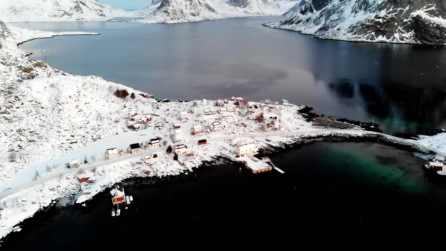 scandinavian fishing village with snow covered on coastline in winter at lofoten islands - tall high stock videos & royalty-free footage