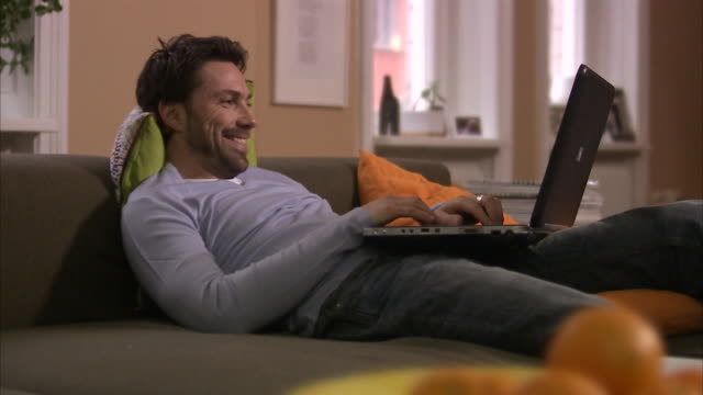 scandinavian man sitting in a couch using his laptop stockholm sweden. - ein mann allein stock-videos und b-roll-filmmaterial