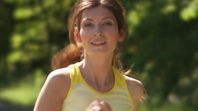 scandinavian woman running in a park sweden. - 屋外点の映像素材/bロール