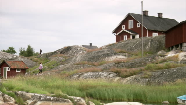 A Scandinavian woman walking on cliffs Huvudskar Stockholm archipelago Sweden.