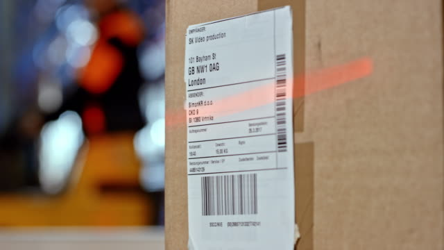 scanning the code on the shipping label of a package - label stock videos & royalty-free footage