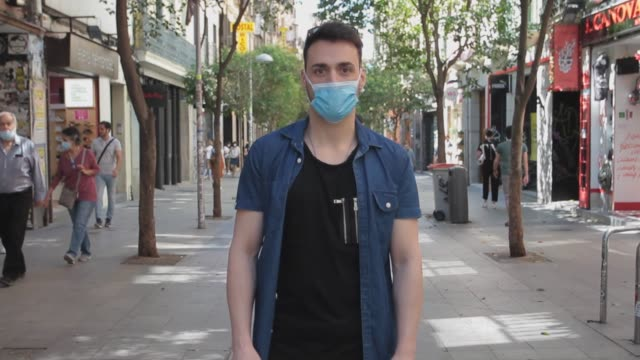 óscar wears adidas sneakers and socks, primark jeans, and bershka t-shirt and shirt during phase 1 of reopening from the covid-19 lockdown on... - street style点の映像素材/bロール