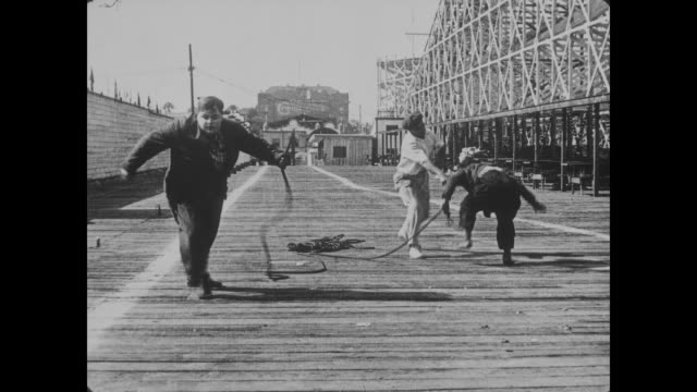 1918 scared bad guy runs up roller coaster to escape determined dog as men (buster keaton and fatty arbuckle) flail and fight with length of rope before falling into ocean - 1918 stock videos & royalty-free footage
