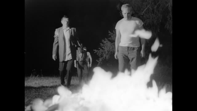 1968 scared but quick thinking man lights dead zombie on fire in front of attacking zombies - 引きずる点の映像素材/bロール