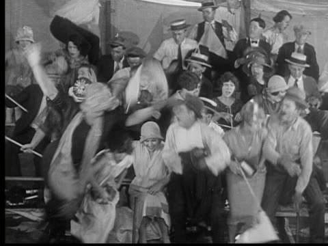stockvideo's en b-roll-footage met 1926 b/w ws scared crowd jumping off bleachers and running out of circus tent / usa - ontsnappen