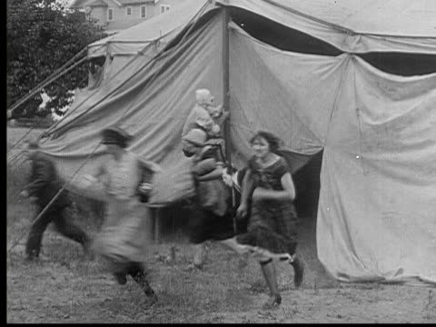 1926 b/w montage ws scared crowd running out of circus tent as clown climbs up tent pole / usa - flüchten stock-videos und b-roll-filmmaterial