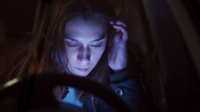 scared injured young woman with bruise on her face hiding in the car while calling for help on mobile phone - runaway stock videos & royalty-free footage