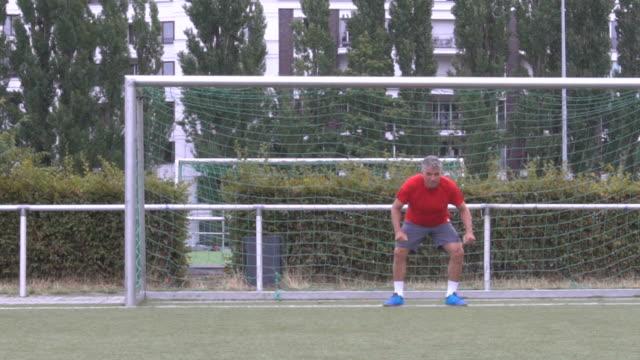 vidéos et rushes de gardien de but senior peur d'essayer d'arrêter le football - gardien de but