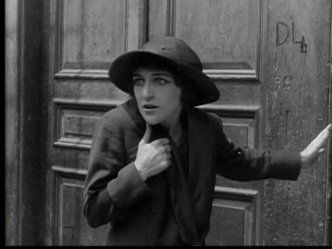 1915 B/W MS Scared woman backing up against wall with expression of fear