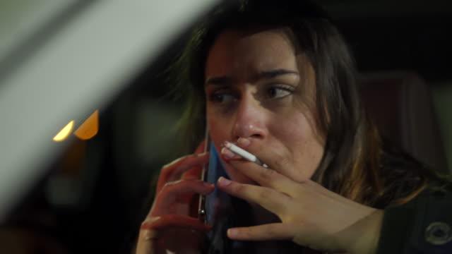 giovane spaventata che si nasconde in auto e chiama il 911 - injured video stock e b–roll