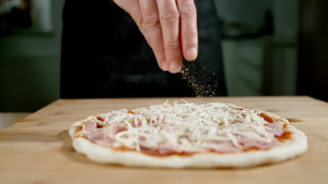 slo mo scattering spices over the pizza - savory food stock videos & royalty-free footage