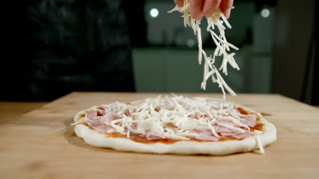 slo mo scattering the cheese over the pizza - italian food stock videos and b-roll footage