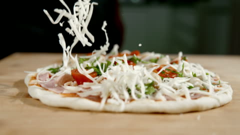 slo mo scattering the cheese over the pizza - pizza stock videos & royalty-free footage
