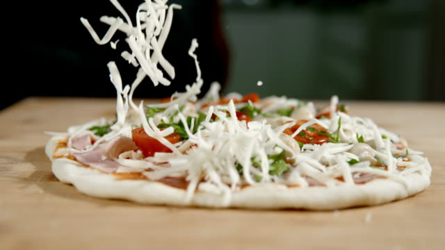 slo mo scattering the cheese over the pizza - recipe stock videos & royalty-free footage