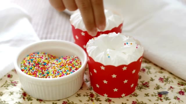 scattering toppings onto the cup cakes - sprinkles stock videos and b-roll footage