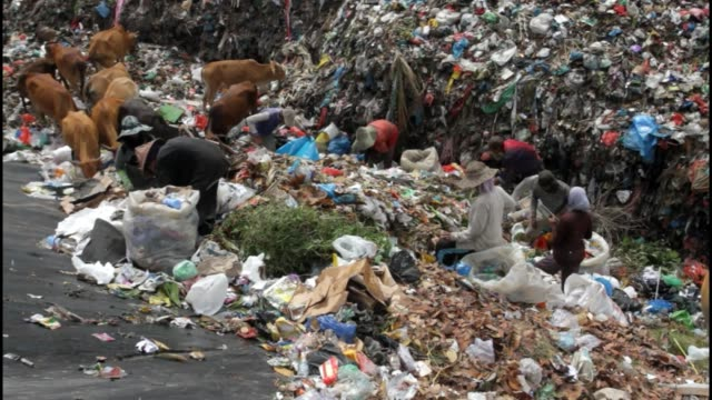 vídeos de stock, filmes e b-roll de scavengers are seen looking for plastic waste material that can be recycled at a landfill in lhokseumawe, aceh, indonesia, on february 5, 2020. - poluição do plástico