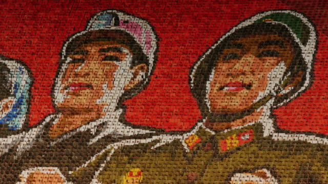 scene change of a giant mosaic by individuals, each holding a card which colored pages links with their neighbours' to make up one gigantic scene - north korea stock videos & royalty-free footage