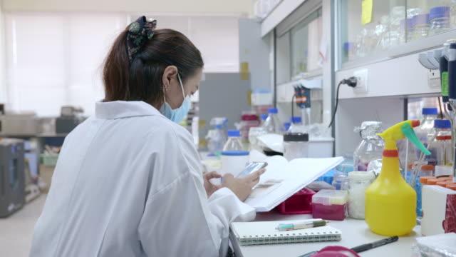 vídeos de stock, filmes e b-roll de cena de close-up de cientista facial usando proteção de máscara está trabalhando em laboratório - só uma mulher de idade mediana