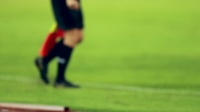 scene defocused slow motion of assistant referees in action during a soccer match, out of focus assistant referee moving along the sideline during a soccer match - referee stock videos & royalty-free footage