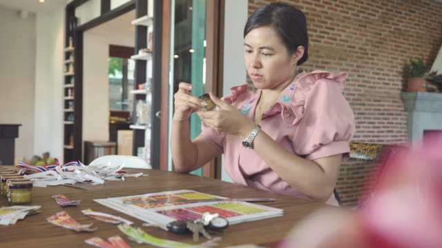 scene dolly shot of asian woman is making sticker put on her products for promoting her business, concept of sme - sticker stock videos and b-roll footage