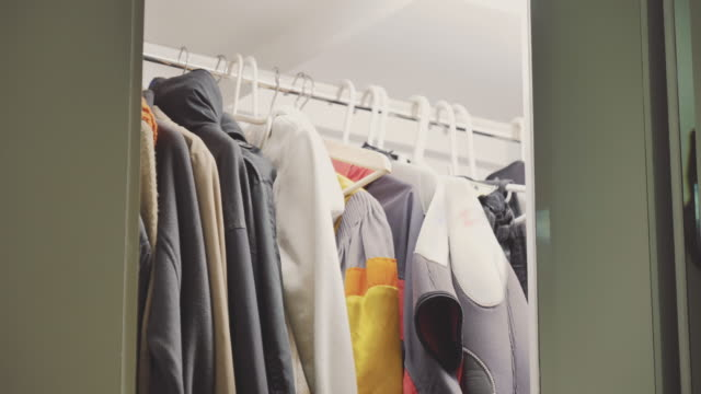 scene dolly shot of clothes hanging in modern wardrobe, concept of day in the life objects - open house stock videos & royalty-free footage