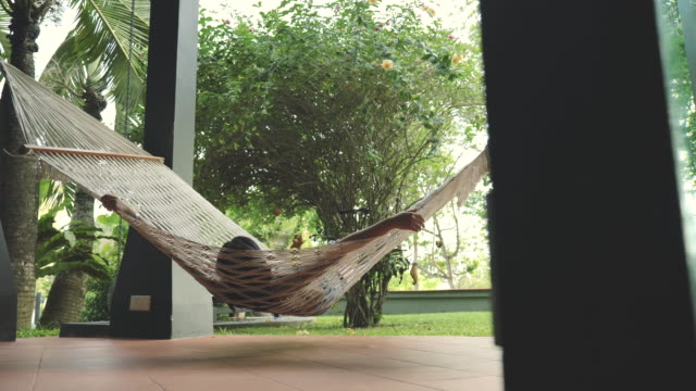 scene dolly shot of hammock that binds in front of the house, asian woman sitting and swing a hammock, relaxing at home. - relaxation stock videos & royalty-free footage