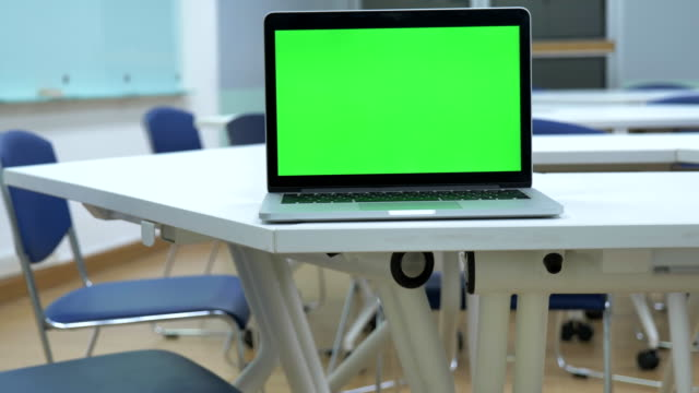 vídeos de stock e filmes b-roll de scene dolly shot of laptop computer showing green chroma key screen stands in the classroom. technology in the background , concept of technology background, back to school - espaço vazio