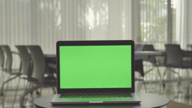 vidéos et rushes de tir de dolly de scène de l'ordinateur portatif affichant l'écran vert de clé de chrome se tient dans le bureau, technologie dans le fond, concept de fond de technologie - bureau pièce