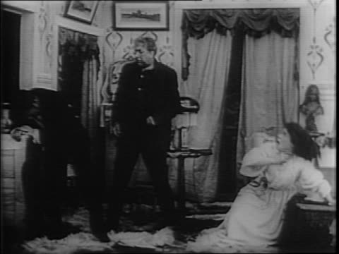 scene from 1910 silent film, woman in dress tries to stop drunk man from drinking from bottle on dresser, man slaps woman, woman falls to the ground,... - slapping stock videos & royalty-free footage