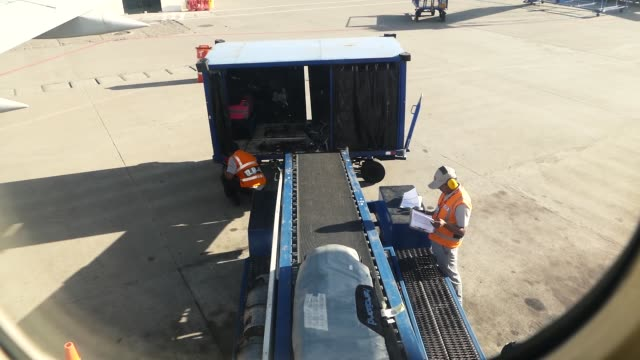 scene from aeroplane window at the slow airport motion clip bagage handlers loading bags cargo unloading - entladen stock-videos und b-roll-filmmaterial
