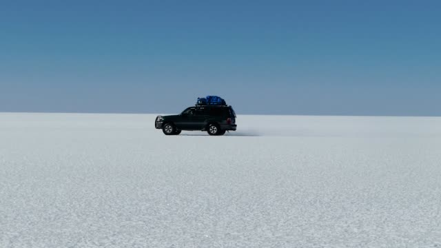 scene from boliva south america slow  motion of truck journey through the salt flats - unendlichkeit stock-videos und b-roll-filmmaterial