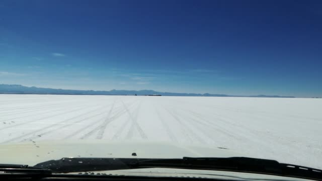 stockvideo's en b-roll-footage met scene from boliva south america slow  motion of truck journey through the salt flats - rondrijden