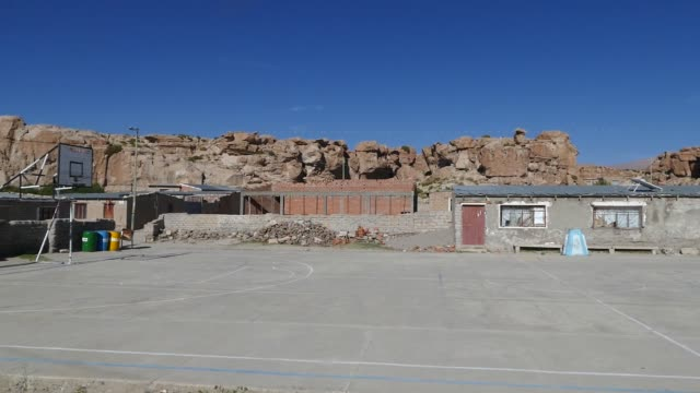 vídeos de stock e filmes b-roll de scene from bolivia countryside south america slow pan motion across left to right village school yard playground buildings basketball - lugar genérico