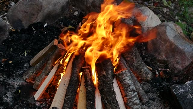 scene from countryside holiday camping slow close motion up of building burning camp fire dancing flames - holiday camp stock videos & royalty-free footage