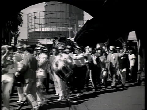 1933 WS Scene from film Convention City of a man walking up to a crowd of people parading down the street then another man walking into the scene waving his arms so everyone stops and turns around and walks back / Atlantic City, New Jersey, United States