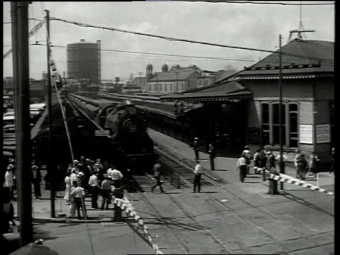 1933 ha scene from film convention city of a train coming to a stop then people crossing in front of train and cars crossing the intersection in front of the train / atlantic city, new jersey, united states - anno 1933 video stock e b–roll