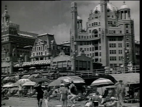 1933 la scene from film convention city of people relaxing and playing on beach with a hotel and boardwalk in background / atlantic city, new jersey, united states - anno 1933 video stock e b–roll