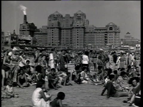 stockvideo's en b-roll-footage met 1933 la scene from the film convention city showing people relaxing and playing on beach with hotel in background / atlantic city, new jersey, united states - 1933