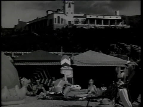 1933 la scene from the film convention city showing people walking around on beach with hotel in background / atlantic city, new jersey, united states - 1933 stock videos & royalty-free footage