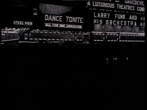 1933 ds scene from the film convention city with atlantic city pier at night with shadows of people walking by and billboards lit up in background / atlantic city, new jersey, united states - scuro video stock e b–roll