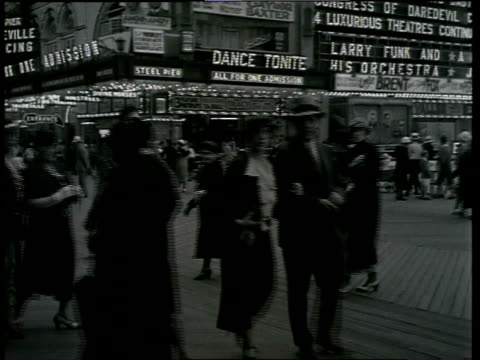 vídeos de stock, filmes e b-roll de 1933 wa scene from the film convention city with groups of people walking and being pushed in small carts in front of marquee and lights and along street / atlantic city, new jersey, united states - atlantic city