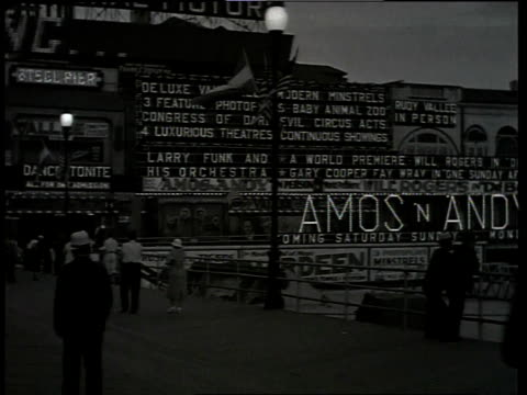 stockvideo's en b-roll-footage met 1933 ws scene from the film convention city with groups of people walking along pier in front of marquee, lights and amos and andy sign / atlantic city, new jersey, united states - 1933
