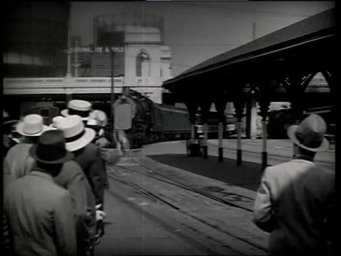 vidéos et rushes de 1933 ws scene from the film convention city with men standing next to train track waving at train passing with people waving out the windows / atlantic city, new jersey, united states - 1930
