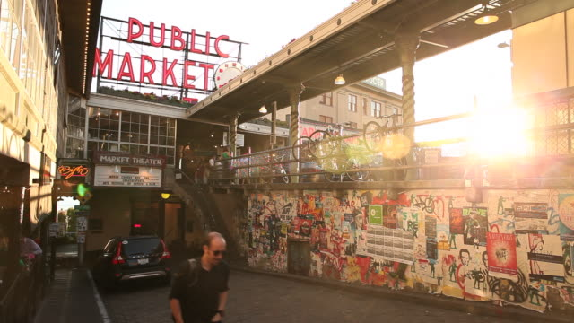 a scene from the pike place market in seattle washington at sunset with the puget sound in the background. - pike place market stock videos and b-roll footage