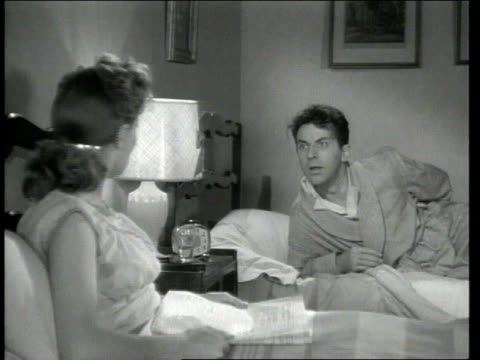 vídeos de stock e filmes b-roll de 1947 montage scene from the short movie so you want to hold your wife where george o'hanlon, playing joe lays in bed talking to his wife and tries to get her to go to sleep so he can put a honker on her back to keep her from snoring - 1947