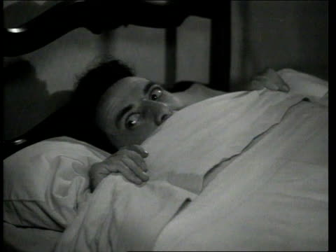 vídeos de stock e filmes b-roll de 1947 montage scene from the short movie so you want to hold your wife where george o'hanlon, playing joe waits for his wife to fall asleep to get out of bed and put a honker on her back to keep her from snoring then gets back into his bed - 1947