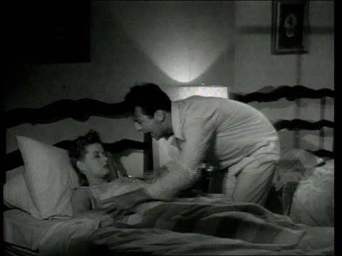 vídeos de stock e filmes b-roll de 1947 montage scene from the short movie so you want to hold your wife where george o'hanlon, playing joe wakes his wife up who is sleeping on her back laying on a stop-snoring-honker that is honking as she is snoring then they argue - 1947