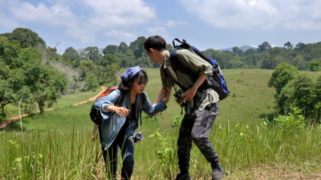 一群亞洲背包客在森林中徒步旅行,在暑假裡一起享受樂趣的場景。他們很高興,在假期裡玩得很開心,放鬆的時刻。青少年自然日常生活的概念戶外 - 東亞人 個影片檔及 b 捲影像