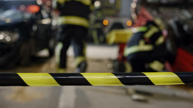 ds scene of a night car accident secured with a barricade tape and firefighters seen in the background - incidente automobilistico video stock e b–roll
